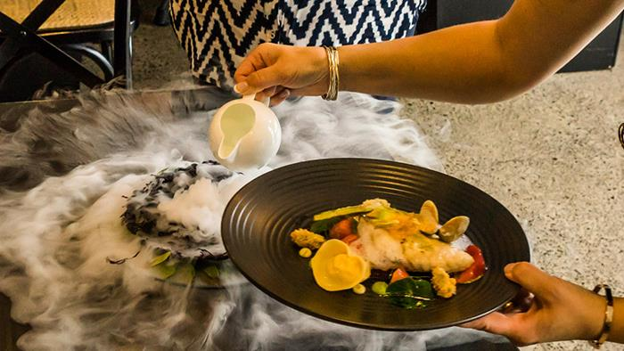 A photograph of a plate of food over some dry ice