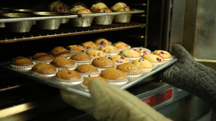 A photograph of a tray of muffins coming out of an oven. Image by Taylor Grote courtesy of unsplash.com.