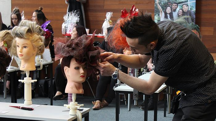 A hairdresser adjusting a mannequin's hair at UCOL's History of Hair Competition