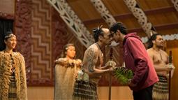 A photograph of two people greeting each other with a hongi in a Maori meeting house