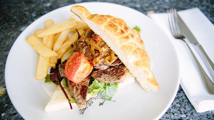 A photograph of an open steak sandwich