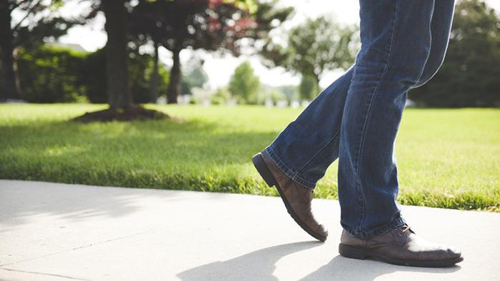 A close up, partial photograph of a person walking in a park