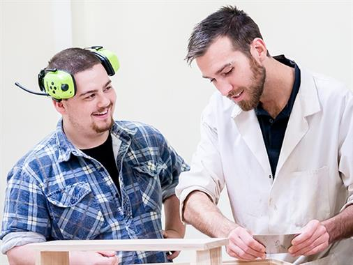 A photograph of a lecturer and a student wearing ear muffs