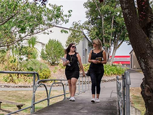 Two ladies walking together through a garden or park