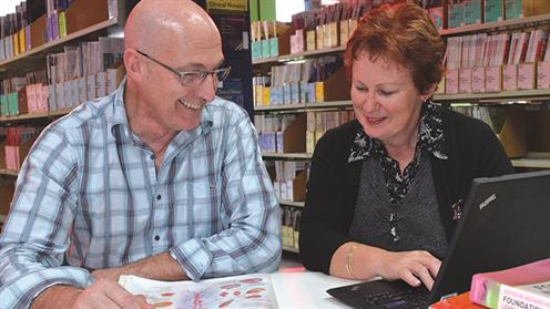 Adult learners studying together in a library