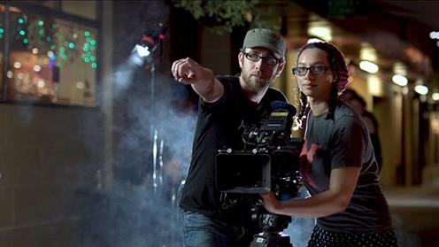 Two people on set of a movie behind the camera lense