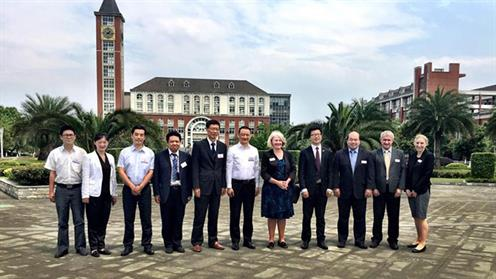 A delegation of people standing on a tertiary campus in China