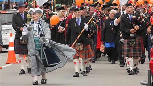 A photograph of Palmerston North Town Crier Caroline Robinson leading a UCOL Graduation parade.