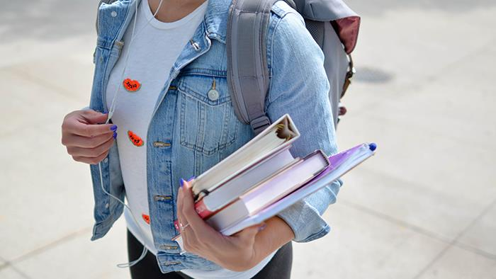 A close up photograph of a student carrying some books