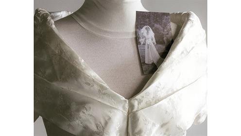 A photograph of a refashioned bridal dress with the original photograph of the bride