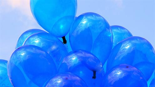A photograph of a bunch of blue balloons