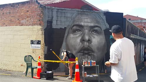 A photograph of UCOL students Eva Harkness and Jacob Chrisohoou painting a mural in Whanganui as part of Whanganui Walls Street Art event.