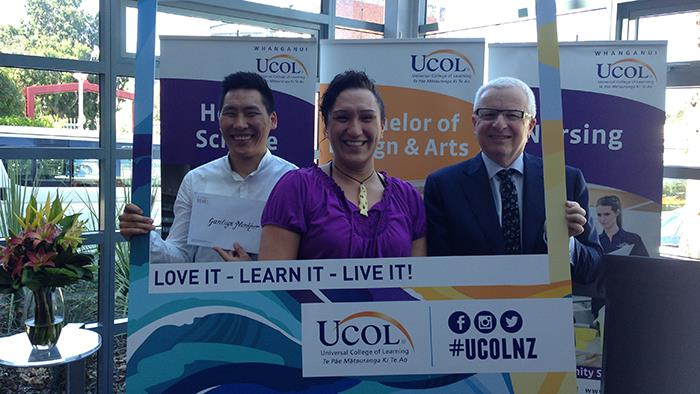 Three people holding a UCOL scholarship