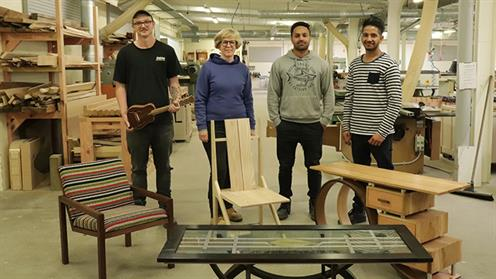A photograph of UCOL furniture design and making students in the workshop with their furniture