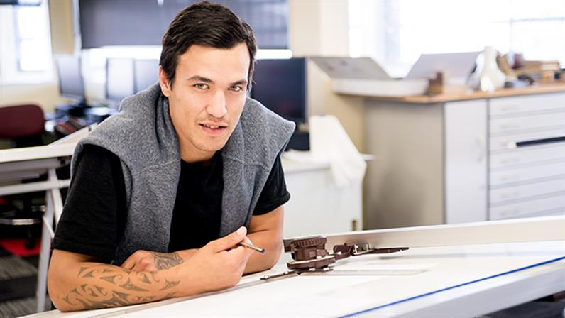 A young man in an architectural drawing class