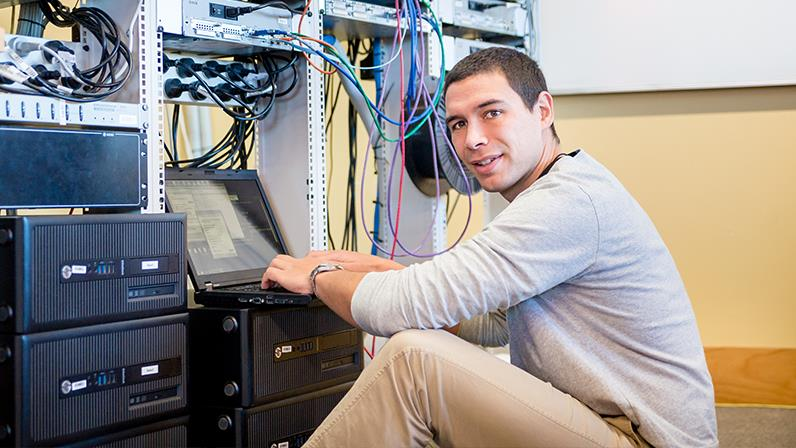A photograph of a young man working on a computer network