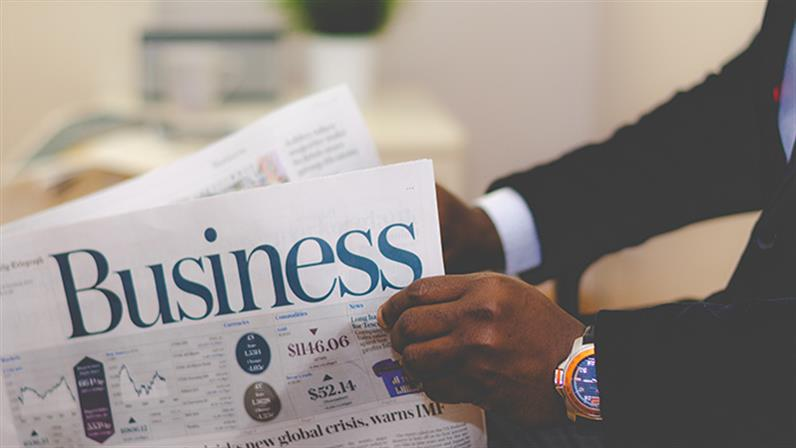 A close up photograph of a person reading a business newspaper