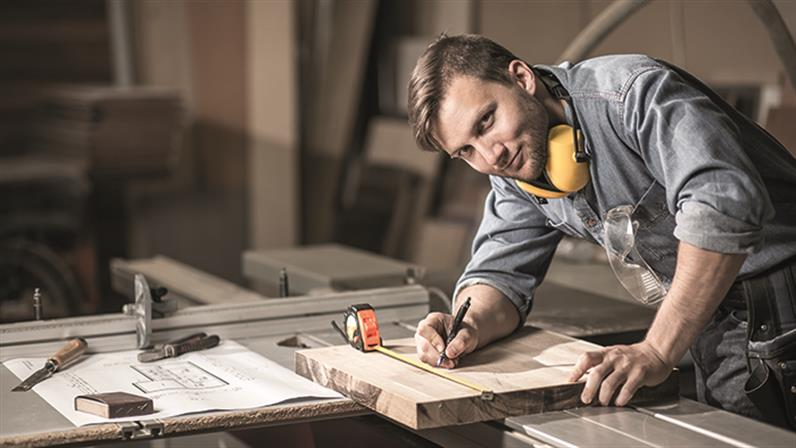 A photograph of a man measuring a piece of wood whilst referring to plans