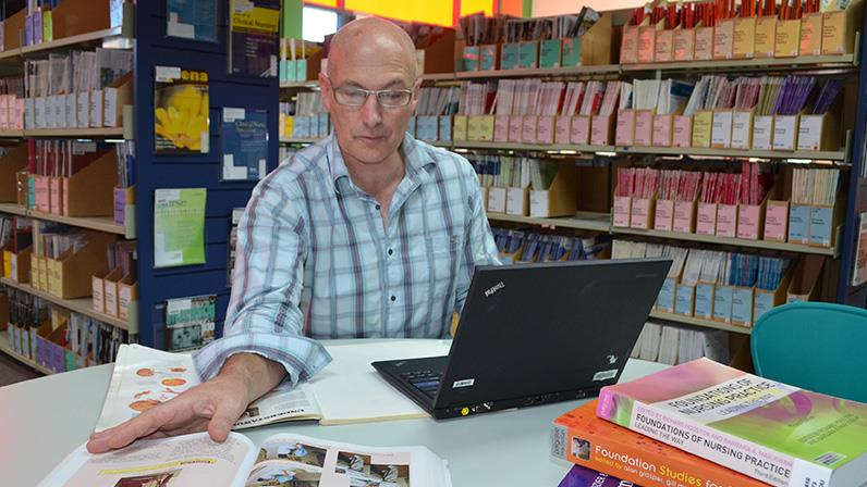 A nursing lecturer works in the Palmerston North campus library