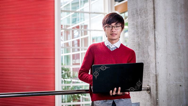 Business student works on his laptop in the Palmerston North atrium