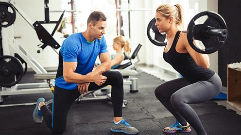 A photograph of an instructor in a gym guiding an athlete