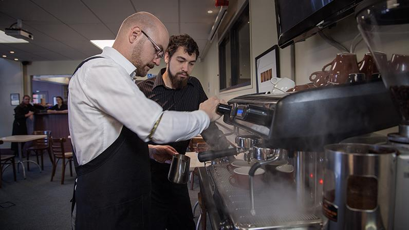Hospitality lecturer Niels Huibers shows a student how to make the perfect coffee