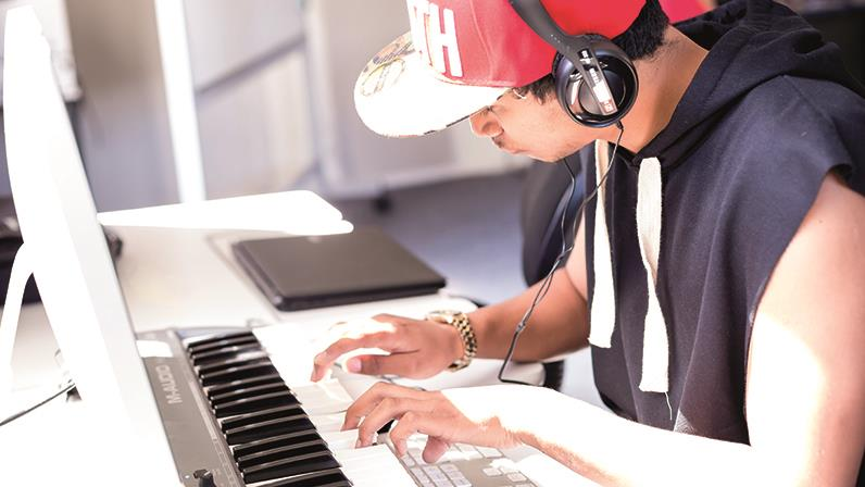 A guy recording music on an electronic keyboard