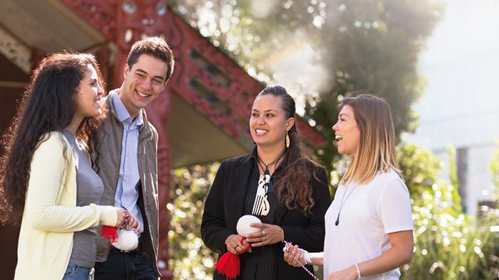 A photograph of a group of people chatting in front of a marae