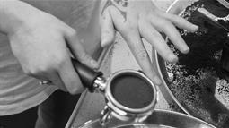 A close up photograph of a person's hands tamping coffee grinds