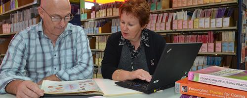 An adult student works with a lecturer in the library at the Palmerston North campus