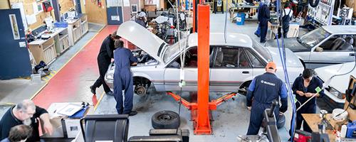 A photograph of the automotive workshop at UCOL in Palmerston North featuring students and lecturers working on cars and equipment