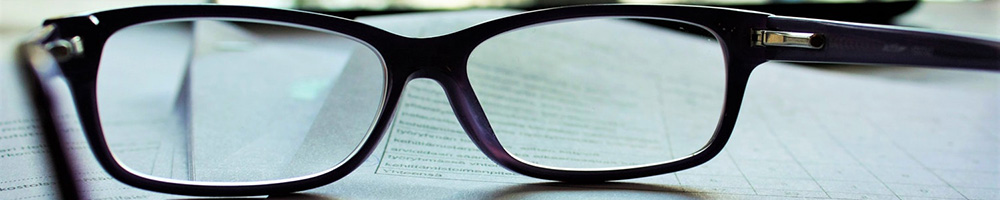 A photograph of a contract viewed through a pair of reading glasses
