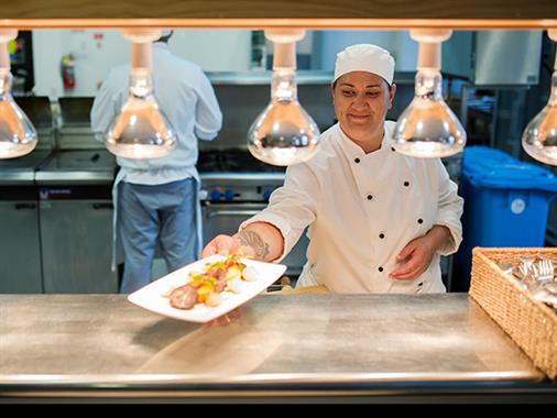 A chef plating up a dish under the heat lamps in a commercial kitchen