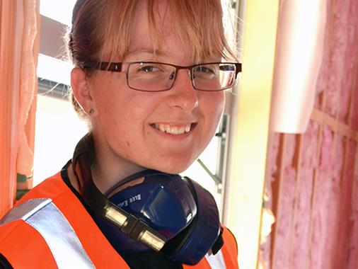 A photograph of a young lady in a construction uniform