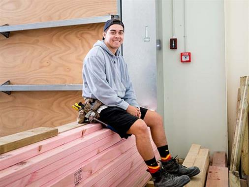 A photograph of a young man sitting on a pile of timber in a workshop