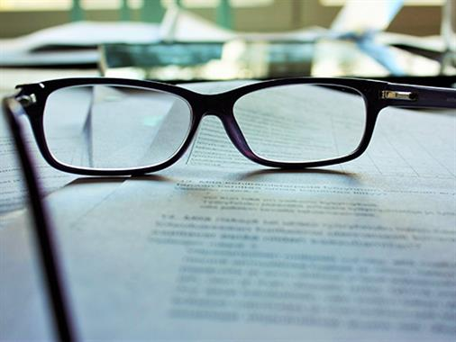A close up photograph of a pair of reading glasses on some paper