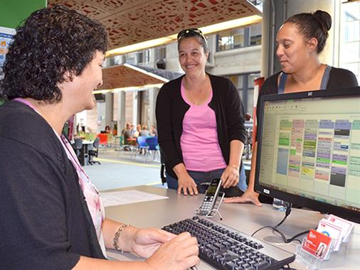 Palmerston North UCOL students receiving assistance from a staff member.