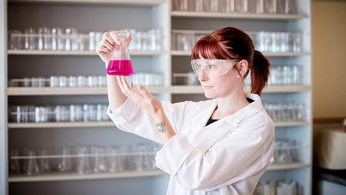 A photograph of a scientist examining liquid in a beaker in a lab at UCOL.