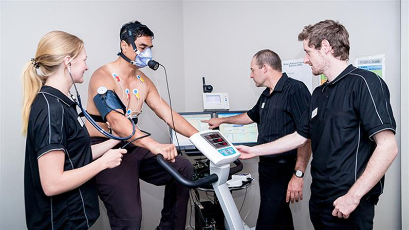 A photograph of UCOL staff and students carrying out V02 max testing on a client.