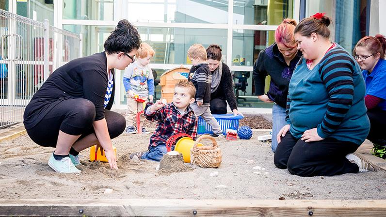 A photograph of an early childhood setting - children and caregivers playing in a sandpit
