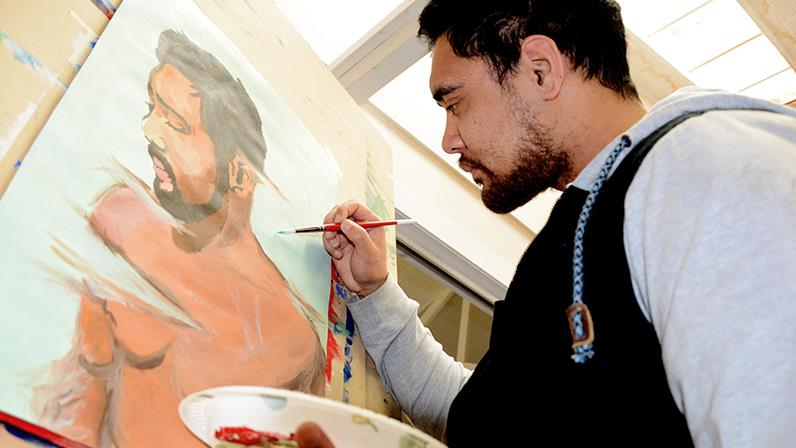 An image of a UCOL student working on a self potrait on a canvas