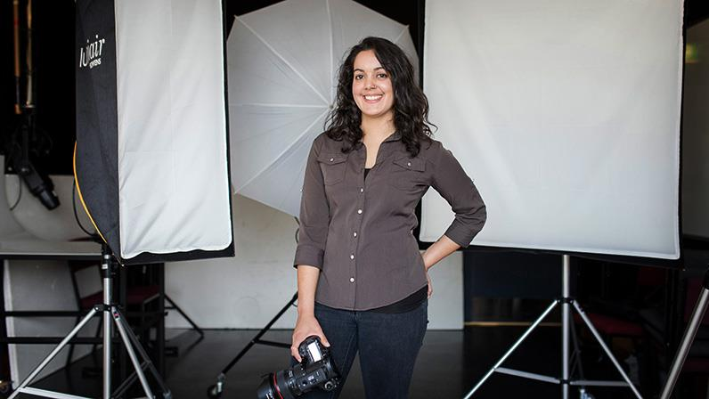 A person standing in a photography studio holding a camera