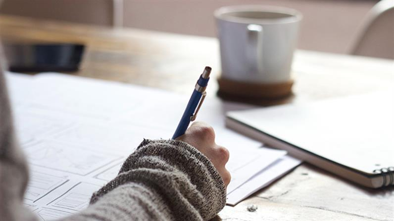 A close up photograph of a person writing