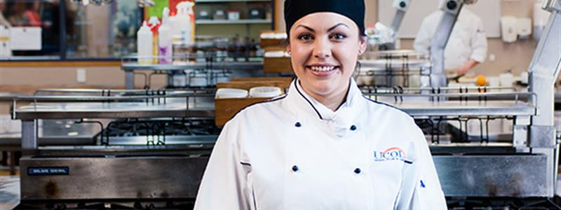 A Cookery Graduate stands in the training kitchen at our Palmerston North campus