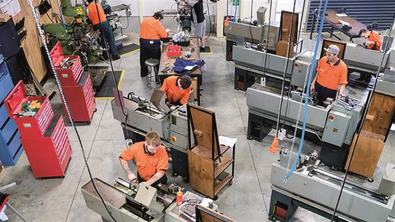 A birds-eye photograph of a mechanical engineering workshop with people working on machines