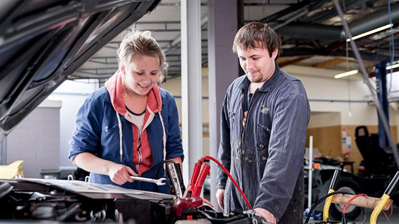 Two UCOL students working on a car.